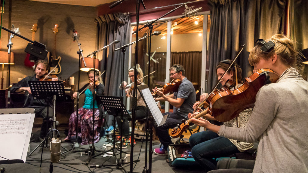 Violinists sight-reading in a recording studio
